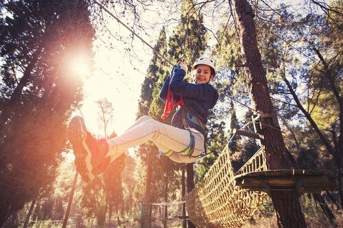 Young girl zip-lining in the woods
