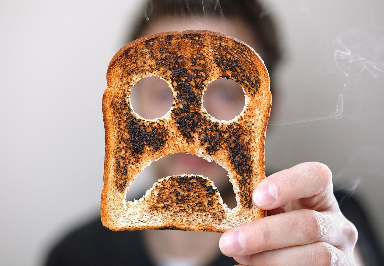 Burnt piece of toast with a side face cut out