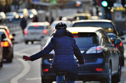 Rear of bicyclist with hand out on the road with other drivers