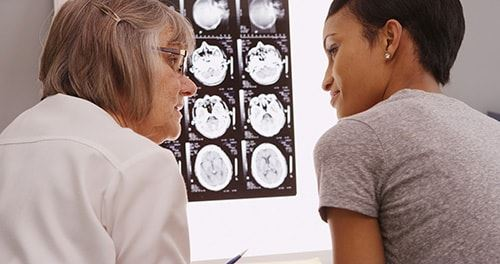 Older female doctor looking at MRI of brain with female patient