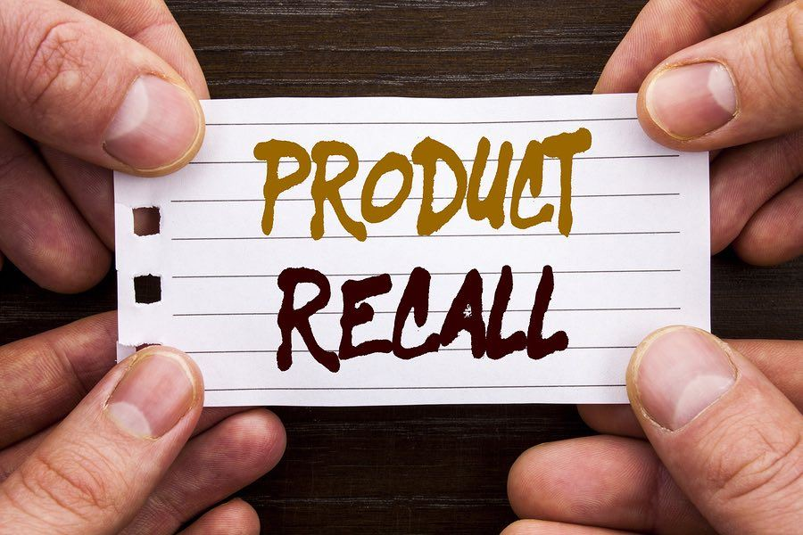 Hands holding a paper that says Product Recall