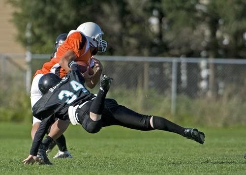 Football player tackling another player